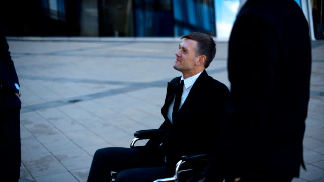 Business people have fun outdoor. Invalid on wheelchair video