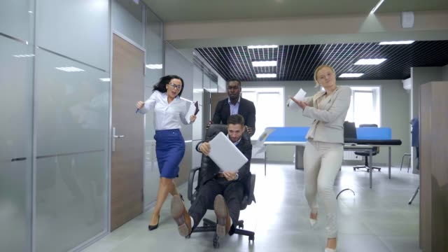 Business people having fun pushing their partners racing on office chairs . video