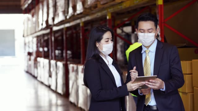 Business people in face mask as new normal talk in warehouse