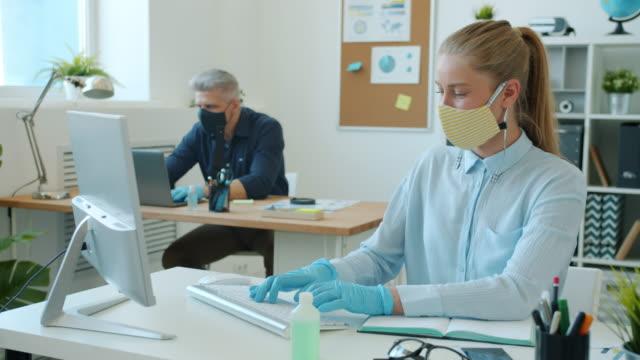 geschäftsleute in gesichtsmasken und handschuhen, die mit computern arbeiten, die im büro tippen - krankheitsverhinderung stock-videos und b-roll-filmmaterial