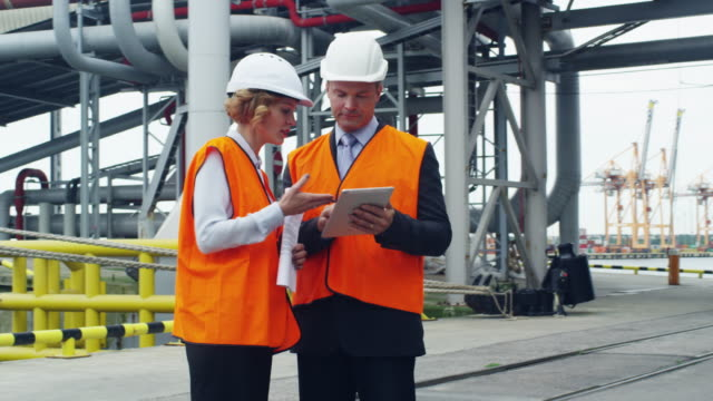 Business People in Safety Vests Using Tablet in Industrial Environment video