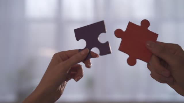 geschäftsleute schließen sich puzzleteilen im büro an. konzept der teamarbeit und partnerschaft - vereinen stock-videos und b-roll-filmmaterial