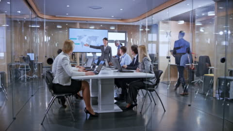 ds uomini d'affari che ascoltano il loro collega asiatico che tiene una presentazione nella sala conferenze di vetro - idea video stock e b–roll