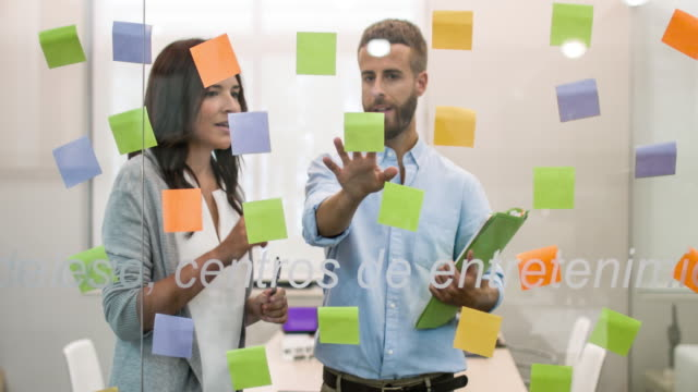 Business people looking at adhesive notes in conference room video