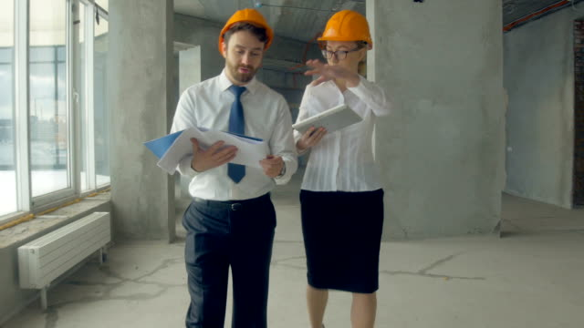 Business people, man and woman discussing construction plan, walking at a construction site. Steadycam shot video