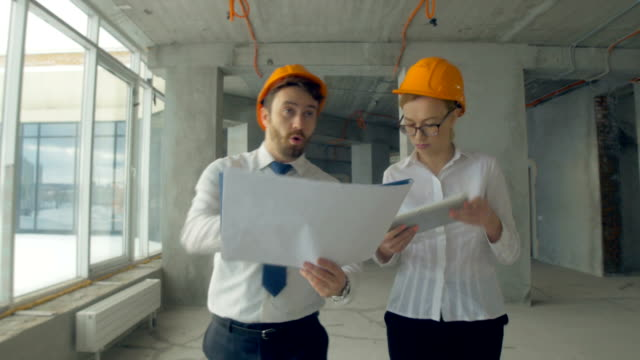 Business people, man and woman discussing construction plan, walking at a construction site. Steadycam shot. Close up video