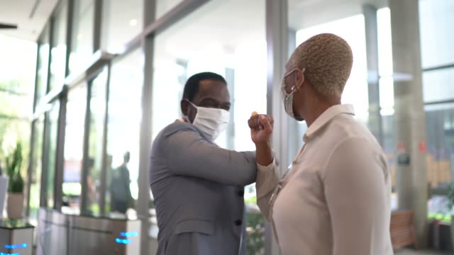 business people on a safety greeting for covid-19 on office's lobby - with face mask - businessman covid mask video stock e b–roll
