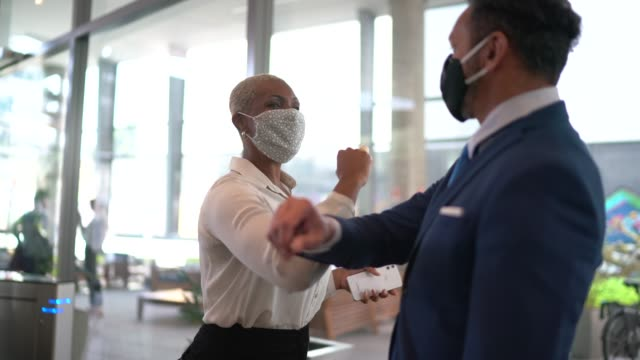stockvideo's en b-roll-footage met zakenmensen op een veiligheidsgroet voor covid-19 op de lobby van het bureau - met gezichtsmasker - partnership