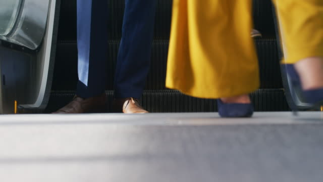Business people on an escalator in a modern building Low angle view of the legs of business people stepping off an escalator in the sunny lobby of a modern office building stepping stock videos & royalty-free footage