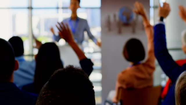 vídeos de stock e filmes b-roll de business people raising their hands in the business seminar 4k - braços no ar