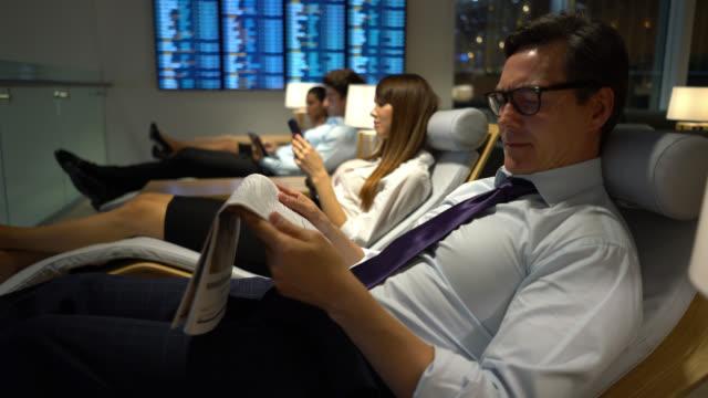 vídeos y material grabado en eventos de stock de gente de negocios relajándose en la sala vip del aeropuerto - viaje en primera clase