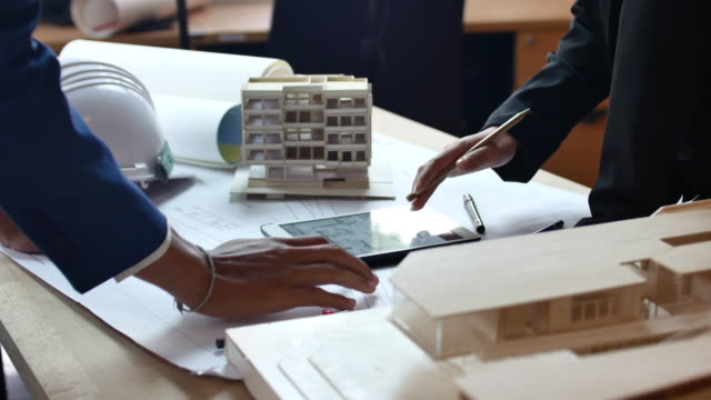 Business people reviewing blueprints on Digital tablet at desk