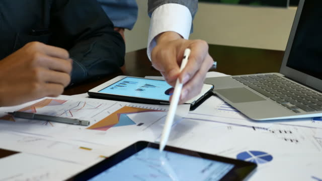 stockvideo's en b-roll-footage met mensen uit het bedrijfsleven die grafieken document voor zakelijke project aan balie bekijken - bedrijfsstrategie