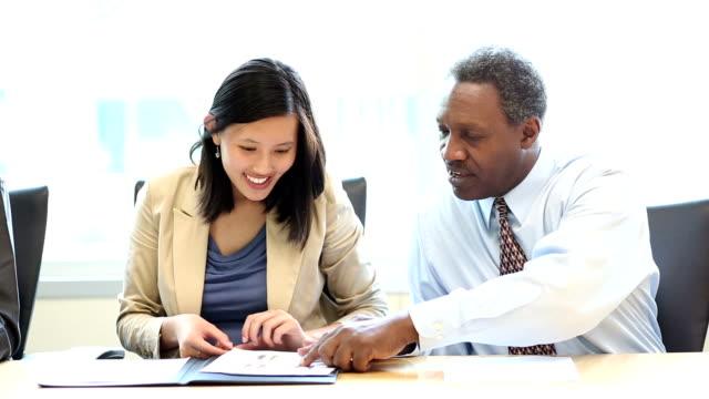 uomini d'affari esaminando una buona relazione insieme nella sala riunioni - rapporto video stock e b–roll