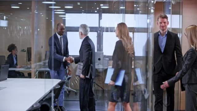 vídeos de stock, filmes e b-roll de ds empresários apertando as mãos na sala de conferências de vidro à chegada - dia do cliente