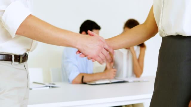 business persone agitare le mani con i colleghi dietro di loro - inghilterra sud orientale video stock e b–roll