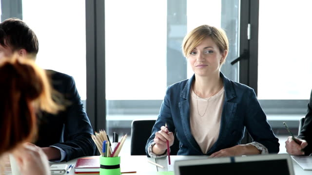 Business people sitting at table in conference room and listening presentation video