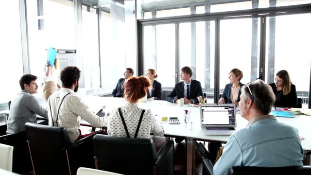 Business people sitting at table while female colleague giving presentation video
