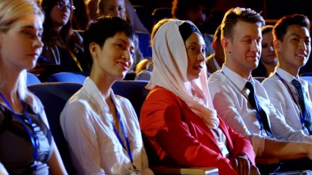 geschäftsleute sitzen auf sitzen im auditorium 4k - zuschauerraum stock-videos und b-roll-filmmaterial