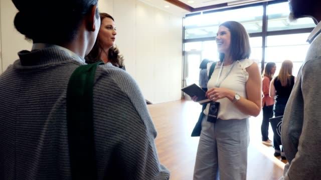 affärsfolk pratar under konferensen träffas och hälsar event - affärskonferens bildbanksvideor och videomaterial från bakom kulisserna