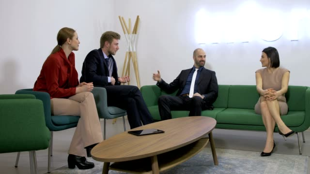 Business people talking and sitting on couches Four business people sitting on couches and talking, friendly conversation four people stock videos & royalty-free footage