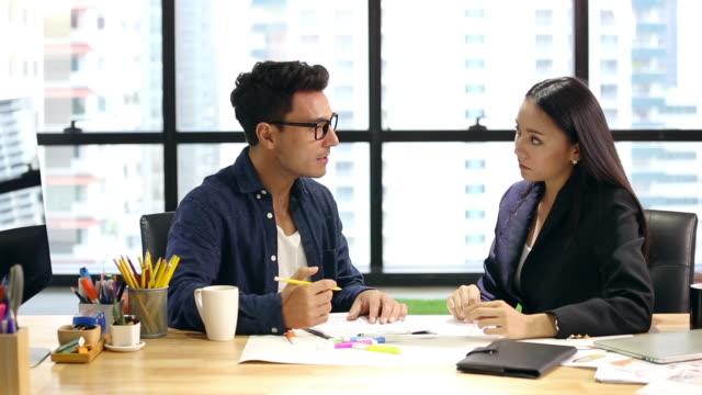 vidéos et rushes de gens d'affaires parlant dans le bureau - expliquer