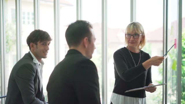 vidéos et rushes de équipe de gens d'affaires développant le plan sur le bureau utilisant des notes de bâton - bloc note