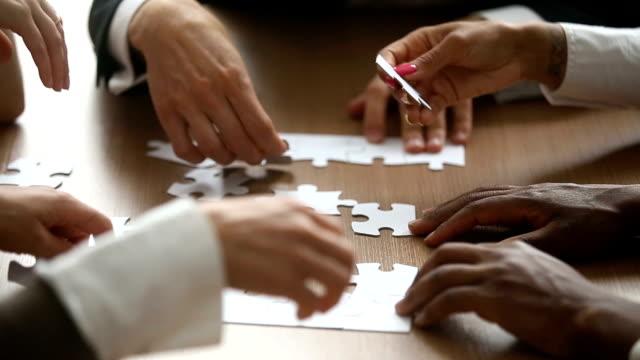 geschäftsleute, jigsaw puzzle eine verbindung herstellen möchten, teamarbeit unterstützen konzept - konferenztisch stock-videos und b-roll-filmmaterial