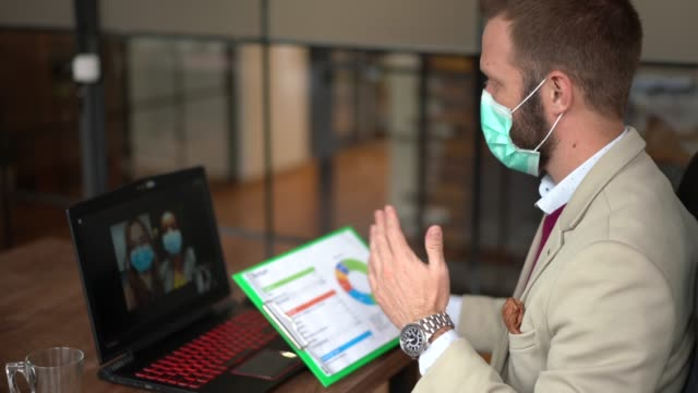 business people video conferencing during covid-19 pandemic - businessman covid mask video stock e b–roll