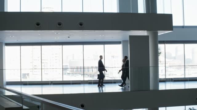 business people walking along hallway in glass business center - quartiere generale video stock e b–roll