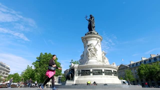 vídeos y material grabado en eventos de stock de gente de negocios caminando y conduciendo bicicletas en parís. la place de la republique con la estatua de bronce de marianne en el centro cuadrado - moda parisina