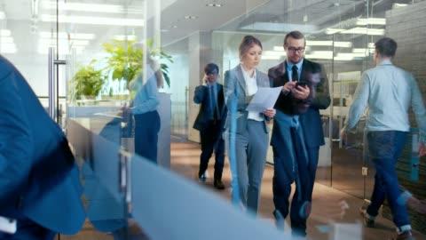 vídeos y material grabado en eventos de stock de gente de negocios caminar y hablar en el pasillo, los empresarios tienen conversación en la oficina, uso de computadora. oficina corporativa con muchos trabajadores ocupados. - negocio corporativo