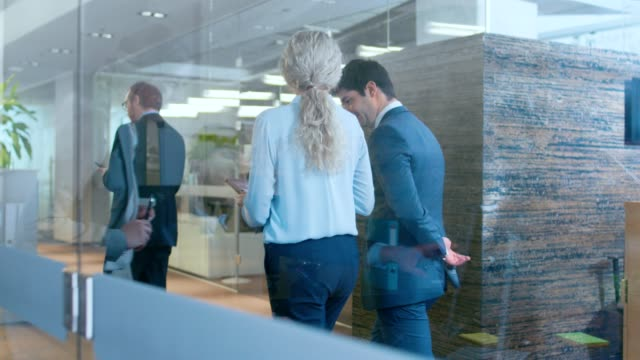 business people walking and talking in the hallway, top manager and businesswoman have conversation in the office, use desktop computer. corporate office with many busy workers. - lawyer stock videos and b-roll footage