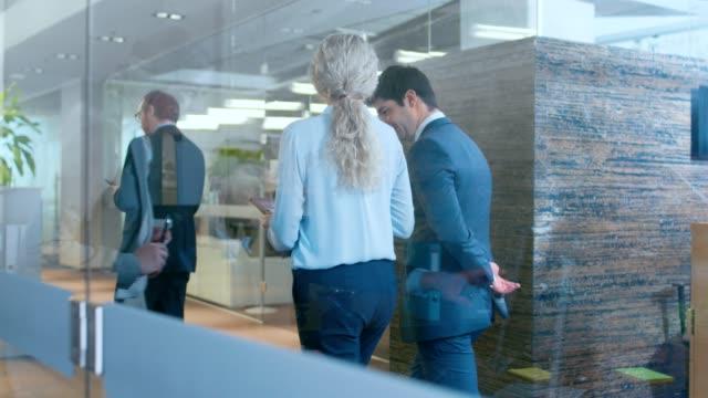 vídeos de stock, filmes e b-roll de negócios pessoas andando e falando no corredor, gestor de topo e empresária ter conversa no escritório, use o computador desktop. escritório corporativo com muitos trabalhadores ocupados. - advogado