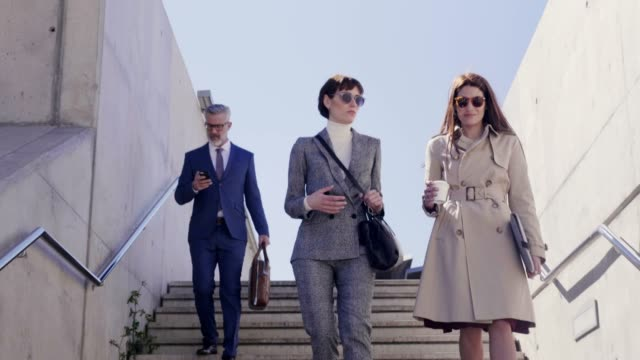 Business people walking down stairs on sunny day