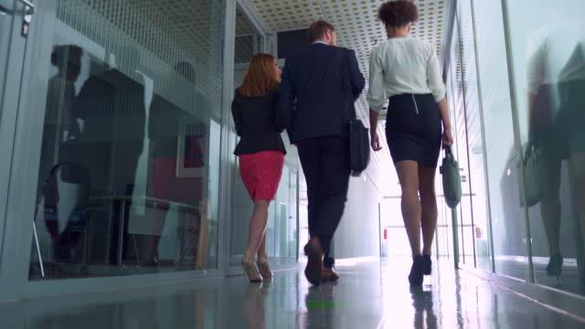 vídeos de stock e filmes b-roll de business people walking in corridor - happy hour