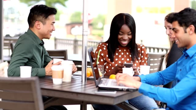Business people working together at outdoor cafe. video