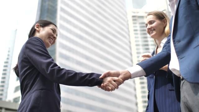 vídeos de stock e filmes b-roll de business person greet each other and shake hands in modern office building - parceria