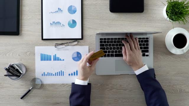 geschäftsperson einfügen gold kreditkarte zahl auf laptop, mann einkaufende unternehmen - billionär stock-videos und b-roll-filmmaterial