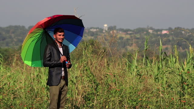 Business person spinning umbrella outdoors in the nature video