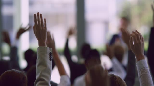 vídeos de stock e filmes b-roll de business professionals raising their hands in a business seminar 4k - braços no ar