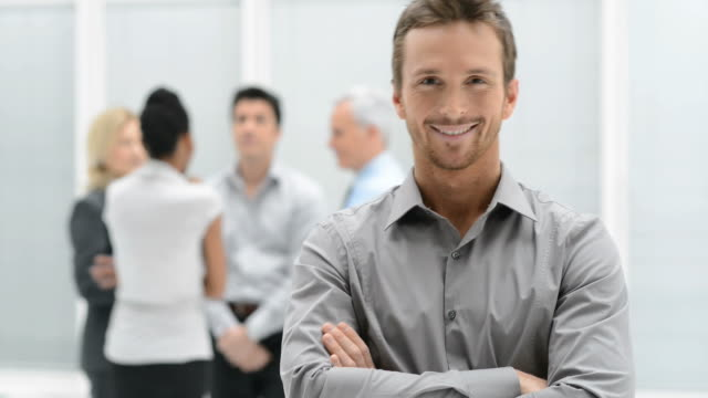 Business satisfaction HD1080p: Proud smiling businessman standing with his colleagues at office. satisfaction stock videos & royalty-free footage
