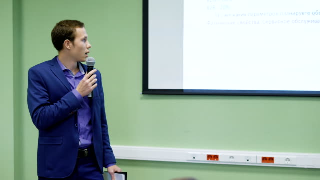 Business school student speaks at a seminar for finance. Young man uses a microphone and a projector for his speech. Student holds in his hand a tablet with papers video