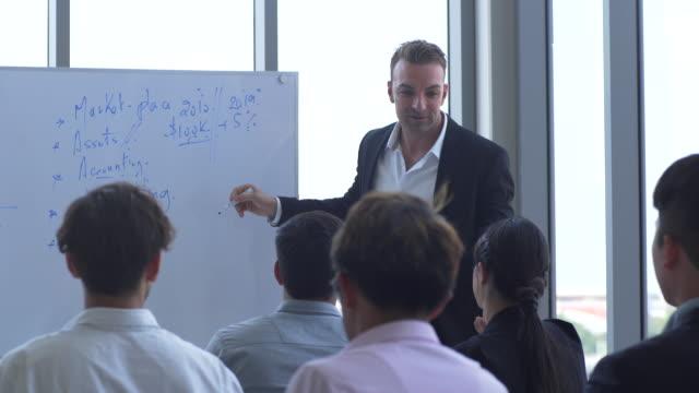 business speaker på seminar, diversifierad business group i ett mötesrum - seminarium bildbanksvideor och videomaterial från bakom kulisserna