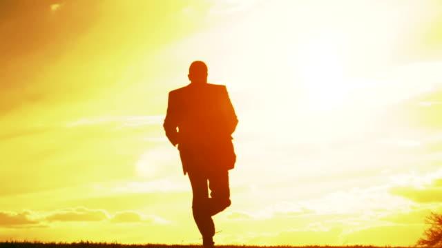 ビジネスの成功のコンセプトの楽しい幸せなシルエットの夕日 ビデオ
