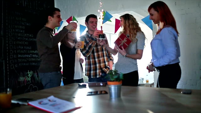 Equipo de negocios celebrando panes en la oficina - vídeo
