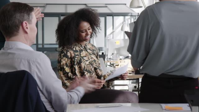 stockvideo's en b-roll-footage met bedrijfsteam dat voor een vrouwelijke collega in vergadering klapt - bewondering