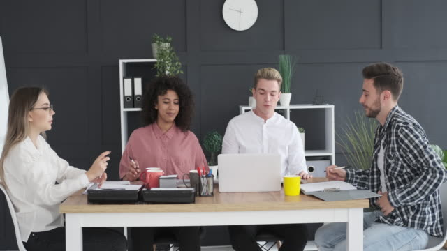Business team discussing at meeting Business team discussing and using laptop at office meeting casual clothing stock videos & royalty-free footage