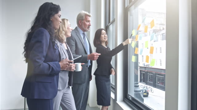 Business team discussing ideas to write on notes at office video