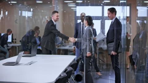 vídeos de stock, filmes e b-roll de equipe do ds negócio entrar na sala de conferência de vidro e cumprimentando o outro time - business